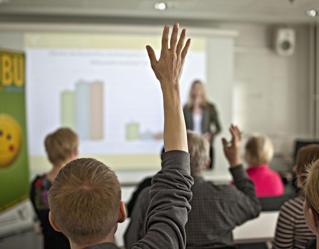 Oppilaat viittavaat luokassa, kun opettaja pitää esitystä.
