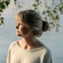 Nainen seisoo ulkona veden äärellä.