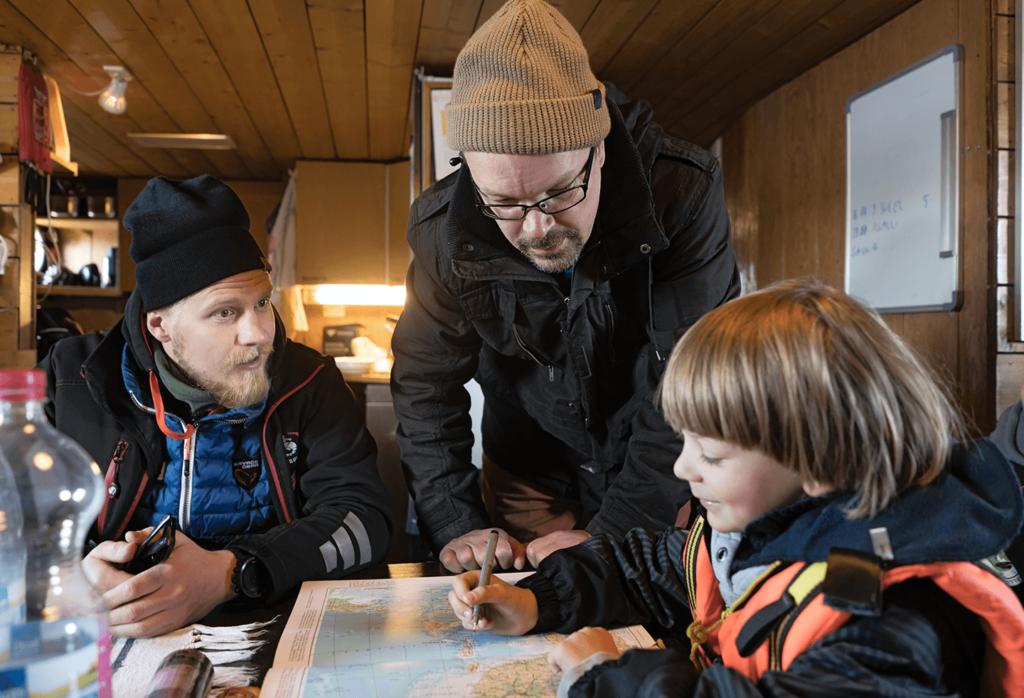 Kaksi miestä laivan sisätiloissa lukemassa merikorttia pikkupojan kanssa.
