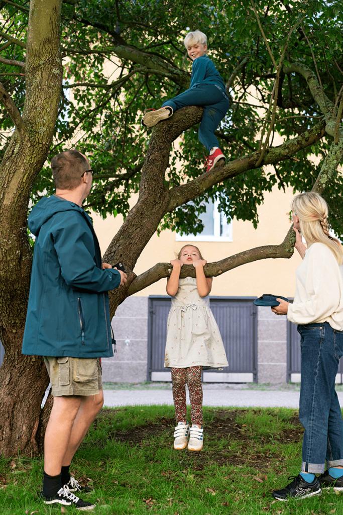 Veli kiipeilee puussa, sisko roikkuu alimmalta oksalta. Isä ja äiti seuraavat vieressä.