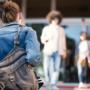 Nuori nainen kävelee koulun portaita reppu selässä