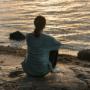 Nainen istuu rantakalliolla.