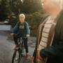 Poika polkupyörän selässä. Isä katselee.