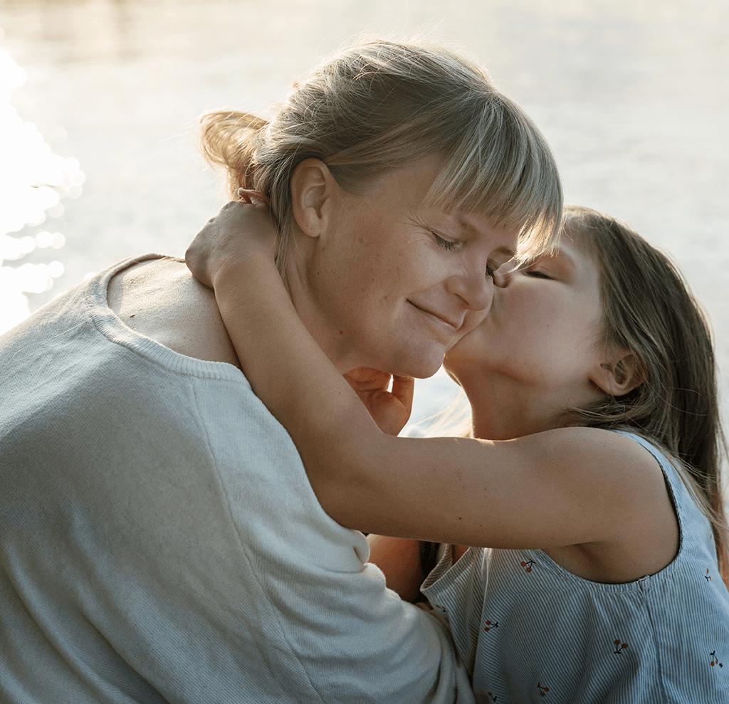 Pikkutyttö antaa äidille pusun poskelle.