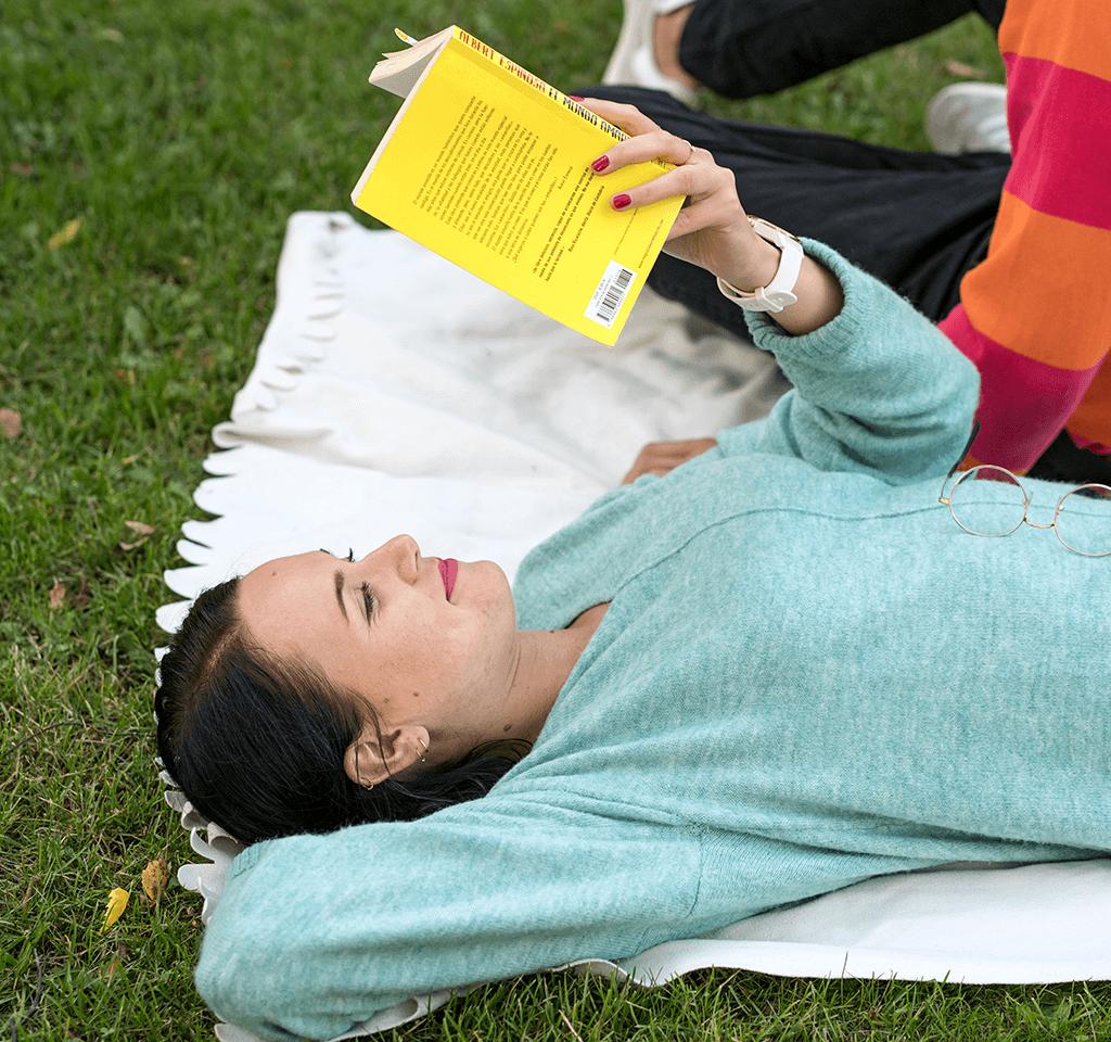 Tyttö lukee kirjaa puistossa piknik-peiton päällä.