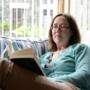 Nainen sohvalla lukemassa.