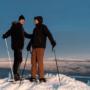 Kaksi miestä hiihtää ja hymyilee.
