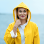 Nainen meren rannalla keltaisessa sadetakissa.
