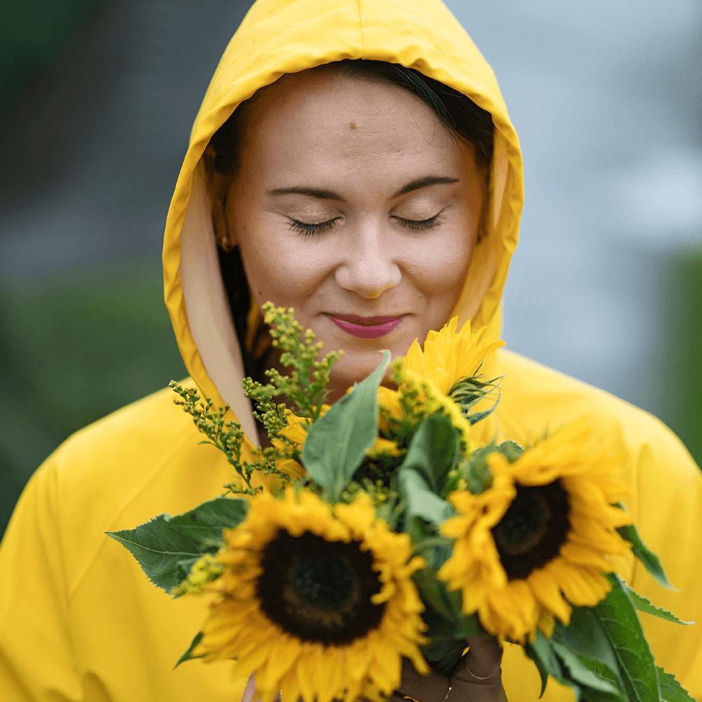 Nainen keltaisessa sadetakissa pitelee auringonkukkia.