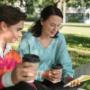 Nuori mies ja nainen lukevat kirjaa ja juovat kahvia puistossa.