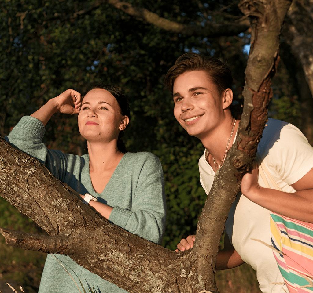 Nuori mies ja nainen katsovat auringon laskua.