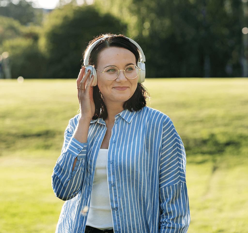 Nainen kuuntelee musiikkia kuulokkeista puistossa.