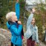Poika, tyttö ja isä luonnossa kädet ilmassa.