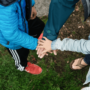 Isä ja lapset kädet päällekkäin.