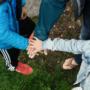 Perhe kädet yhdessä ulkona.