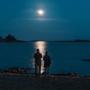 Ihmisiä rannalla pimeässä.
