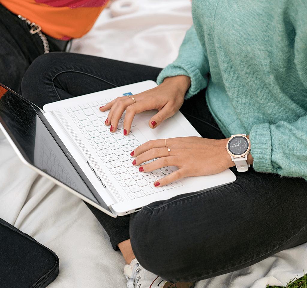 Kvinnan sitter och använder sitt datorn.