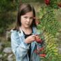 Alakouluikäinen tyttö seisoo metsässä pihlajapuun vieressä.