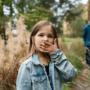 Pikkutyttö metsäpolulla, isä taustalla.