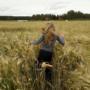 Tyttö juoksee vehnäpellossa.