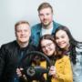 Studiokuva nuorista, joista yhdellä on irtonainen auton ratti kädessä.