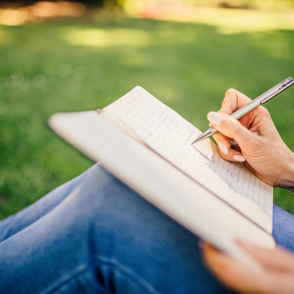 Nainen istuu puistossa ja kirjoittaa vihkoon.