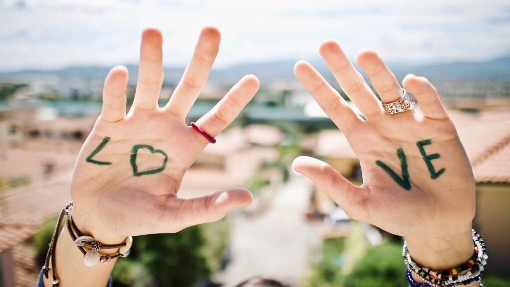 Nuori pitää käsiä ilmassa. Käsiin on kirjoitettu englanninkielen sana LOVE.
