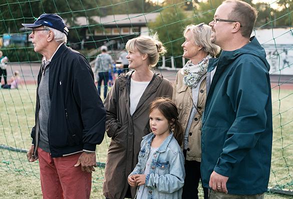 Isovanhemmat, vanhemmat ja lapsi seisovat jakapallokentän laidalla.