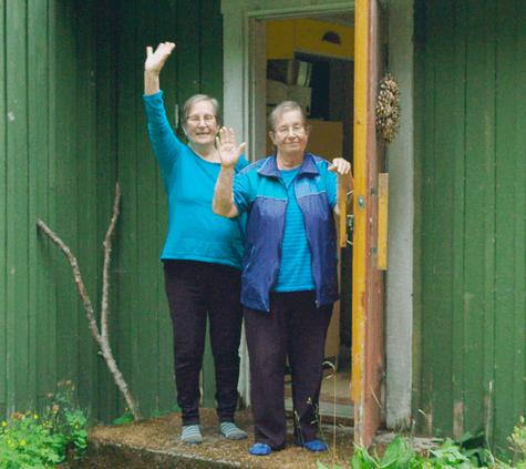 Kaksi vapaaehtoista murusta rappusilla heiluttamassa kättä.