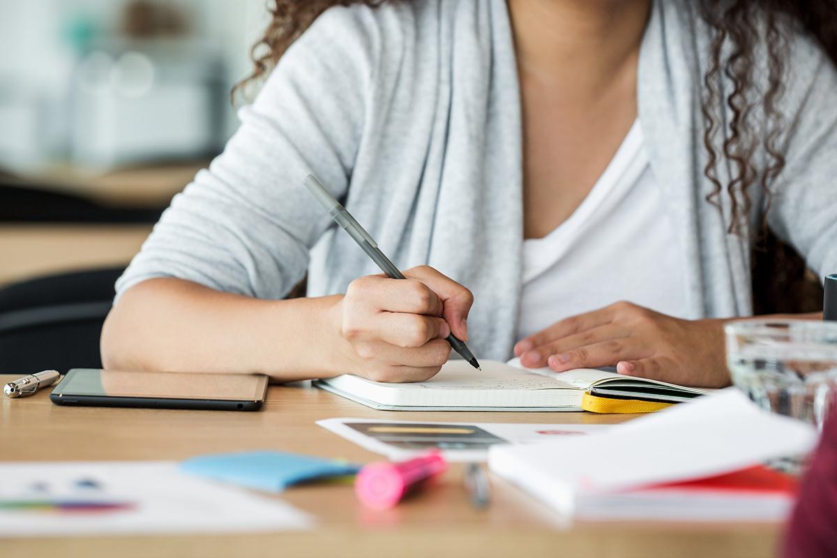 Henkilö kirjoittaa muistiinpanoja vihkoon.